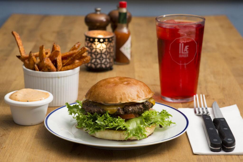 Ilæ Burger. Burger på hvid tallerken med fritter og et glas rød sodavand.