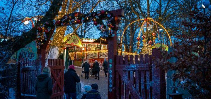 Bakken pyntet op til jul. Julelys og besøgende, der går igennem den røde port.